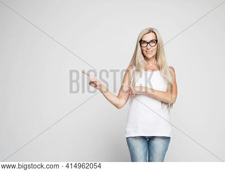 Smiling senior gray-haired woman isolated on gray studio background pointing with finger at blank copy space aside, happy positive aged female show at vacant advertising spot