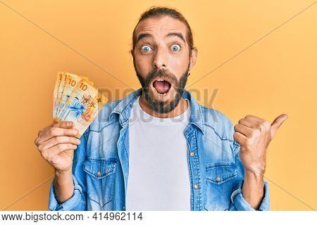 Attractive man with long hair and beard holding 10 swiss franc banknotes pointing thumb up to the side smiling happy with open mouth