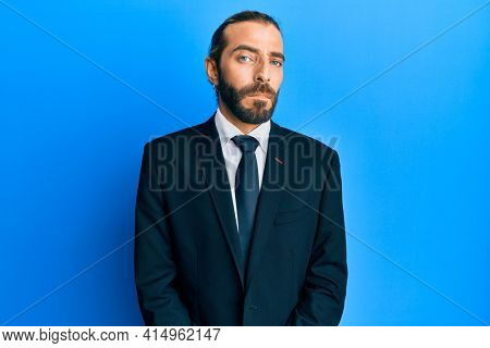 Attractive man with long hair and beard wearing business suit and tie with serious expression on face. simple and natural looking at the camera.