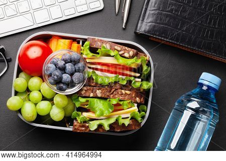 Healthy office lunch box with sandwich and fresh vegetables, water bottle, nuts and fruits on desk. Top view flat lay
