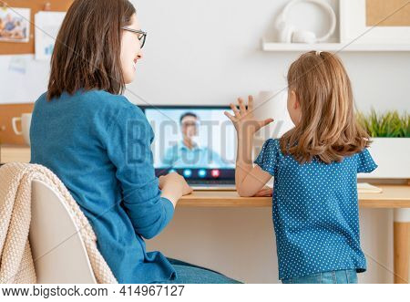 Happy loving family. Young mother and daughter girl using laptop pc for remote conversation with grandma. Funny mom and lovely child are having fun staying at home.