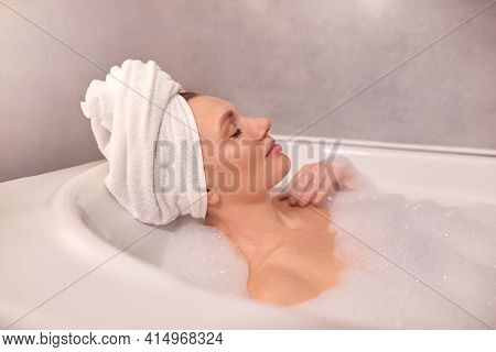 Woman Taking Bath At Home. Young Woman Relaxing In White Bath Full Of Foam. Female With Towel On Hea