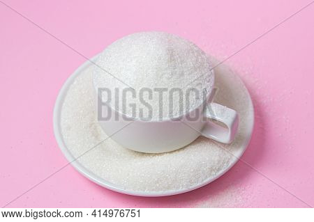 Excessive Sugar Intake. Sugar On A Pink Background. An Overflowing Cup Of Sugar.