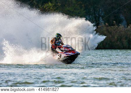 Krasnodar, Russia - October 25, 2020: Jet Ski Racer Drives Watercraft Splashing In Sunset While Raci