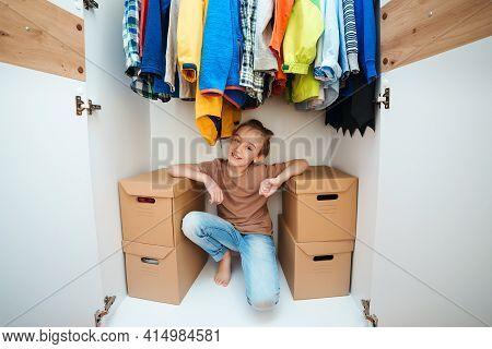 Cute Boy Sitting Inside New Modern Wardrobe. Order In The Children Wardrobe. Happy Kid Helping Unpac