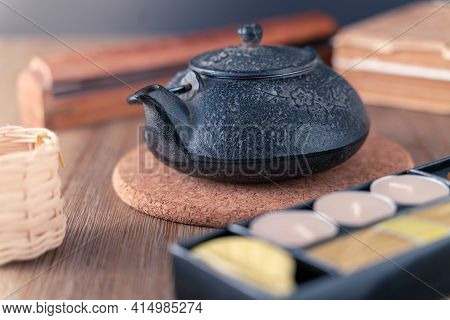 Black Metal Japanese Tea Pot On A Wooden Table With Tea Candles And Wooden Box Of Fragrant Sticks. Z