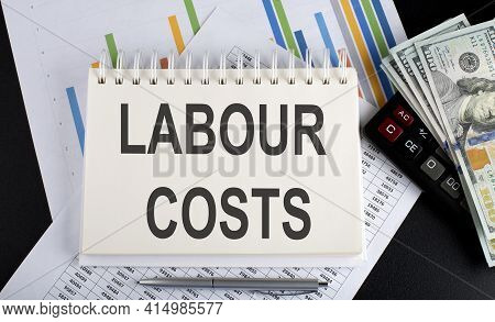 Labour Costs Text Written On Notebook With Chart,calculator And Dollars