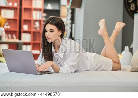 Lifestyle. Full length portrait of a beautiful young woman using a laptop lying on the bed in her cozy studio apartment. Home interior, furniture.