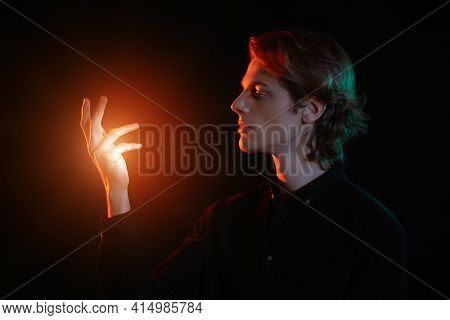 Dark portrait of a handsome young man with wavy blond hair looking at glowing red lighting palm of his hand in black background background. Side view. Men's beauty.