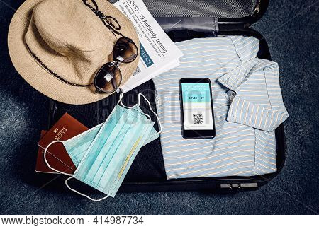 Luggage with mobile phone showing covid-19 vaccination record. Vacation plan for 2021 covid-19 pandemic. Traveling luggage with clothes and mobile phone with information of vaccination for Covid-19. Covid-19 vaccination record. Covid-19 mobile app.