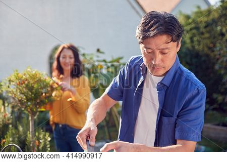 Close Up Of Mature Asian Couple At Work Watering And Caring For Plants In Garden At Home