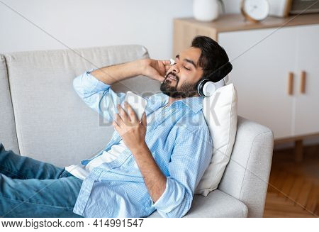 Eastern Man Listening Music On Smartphone Online With Wireless Headphones