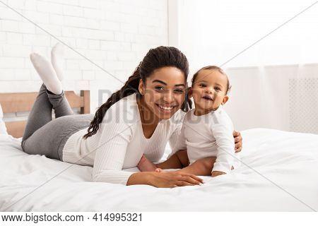 Happy African American Mom Embracing Baby Boy Posing In Bedroom