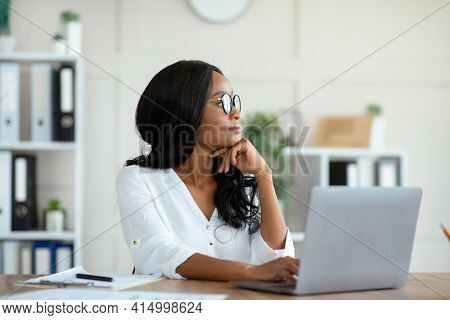 Millennial Black Entrepreneur Daydreaming In Front Of Laptop At Contemporary Office