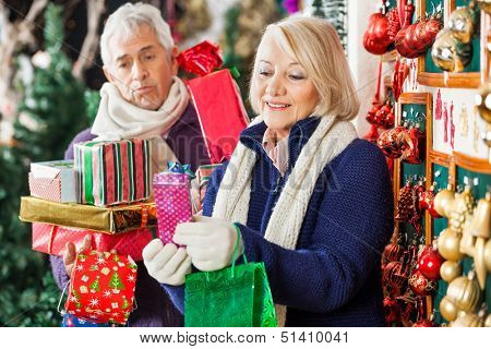 Happy senior woman shopping presents with tired man in Christmas store