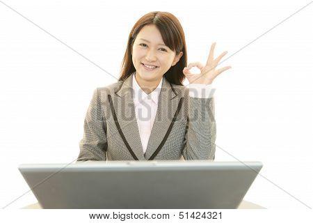 Smiling business woman using laptop