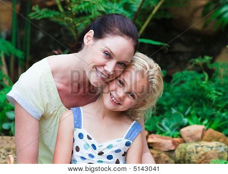 Mother And Daughter Planting In Their Garden