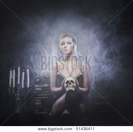 Young, sexy and beautiful witch over the smoky background