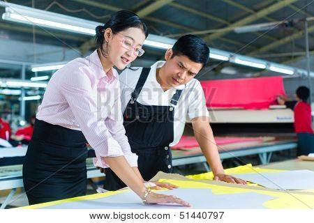 Indonesian Worker or foreman and dressmaker, tailor or designer looking at pattern on a table in a Asian textile factory