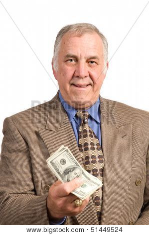 Smiling older businessman in a sports coat and tie over a white background holding fist full of dollar bills