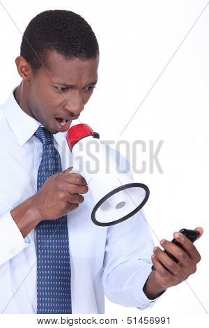 Annoyed man using a loudspeaker to shout at his cellphone