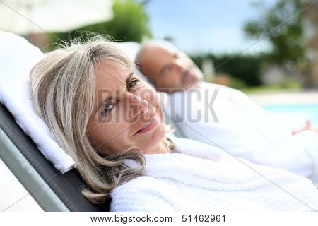 Senior woman in spa hotel relaxing by the pool