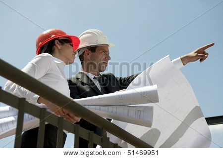 Architects inspecting site, holding blueprints