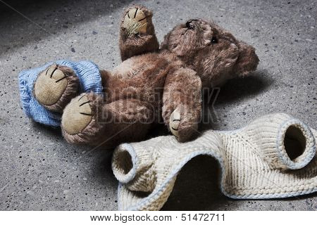 Stripped teddy lying on a concrete floor poster