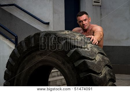 Muscular Man with Truck Tire doing crossfit style workout turning tire over poster