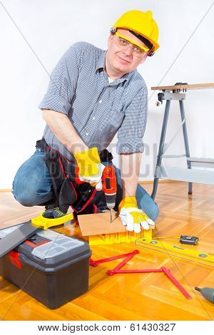 Construction worker holding a drill and drilling wooden board