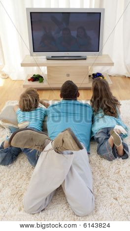 Family On Floor In Living-room Watching Television