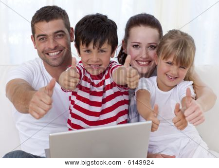 Family At Home Using A Laptop With Thumbs Up