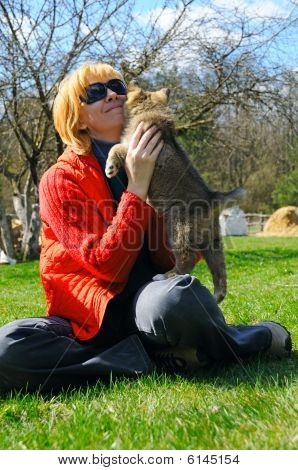 Young Beautiful Woman Pets A Puppy