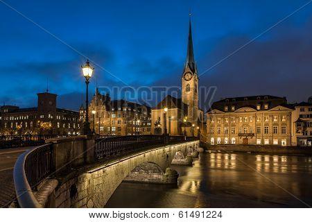 Illuminated Fraumunster Church And River Limmat In Zurich, Switzerland