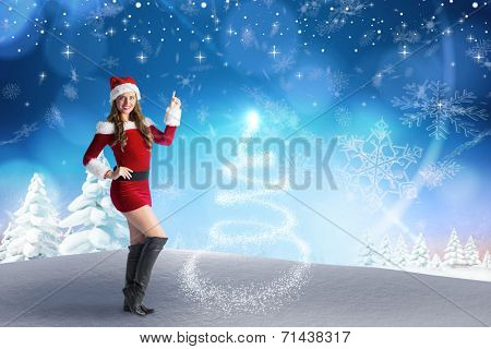 Sexy santa girl pointing against snowy landscape with fir trees poster