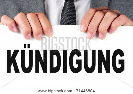 a businessman showing a signboard with the word kundigung, dismissal in german, written in it