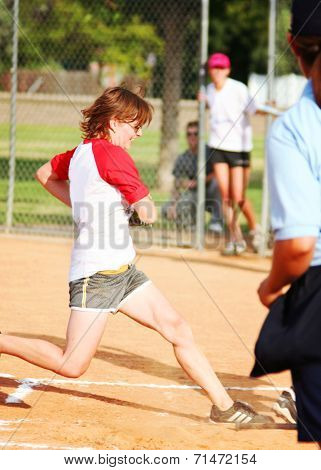 a young girl touching home plate in a softball game