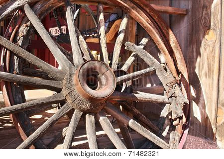 Old broken down wagon wheel from the wild west poster