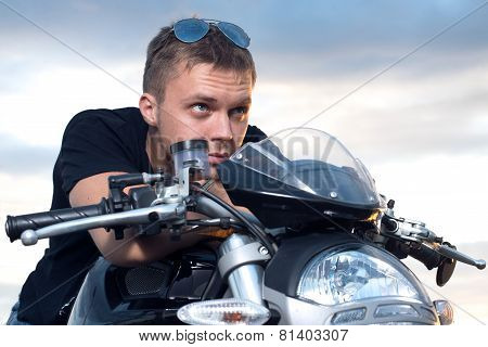 man with a stubborn look leaned on the steering wheel of his bike