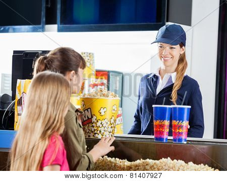 Little girls buying popcorn and drinks from female seller at cinema concession stand