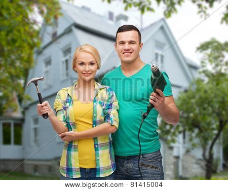 repair, people, real estate, home and family concept - smiling couple with hammer and electric drill over house background