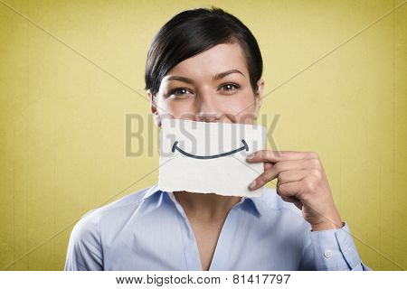 Joyous young businesswoman holding empty white card with space for text in front of her mouth, isolated on yellow background.