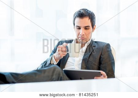 Businessman Grimacing In Disgust At His Tablet
