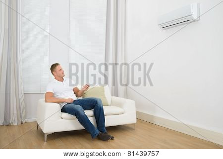 Man Adjusting The Temperature Of Air Conditioner