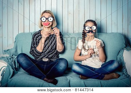 funny mom and daughter with false mustaches, playing at home poster