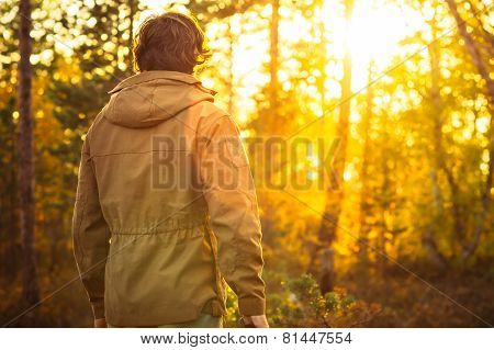Young Man standing alone in forest outdoor with sunset nature on background Travel Lifestyle