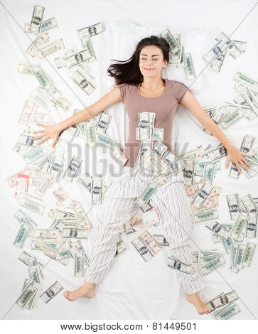 Happy woman sleeping in a bed full of money