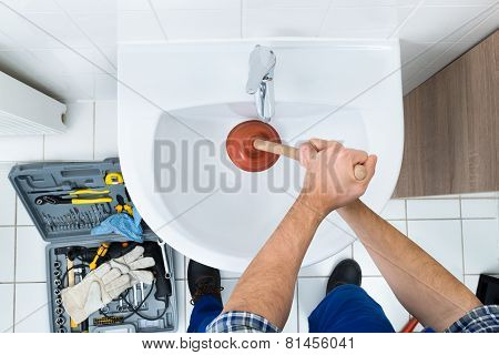 Male Plumber Using Plunger In Bathroom Sink