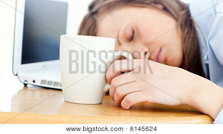 Slumbery Woman Sleeping On Table In Office