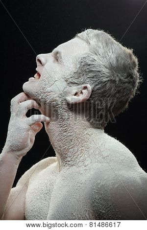 Handsome man covered with powder itching